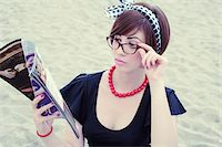 sandi model - Portrait of young woman wearing horn-rimmed eyeglasses reading magazine on beach, Italy Stock Photo - Premium Rights-Managednull, Code: 700-07066