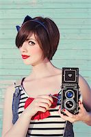 Portrait of young woman looking at camera and holding vintage camera, studio shot Stock Photo - Premium Rights-Managednull, Code: 700-07066935