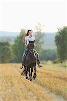 riding crop - Young Woman Riding a Friesian Horse through threshed Cornfield, Bavaria, Germany Stock Photo - Premium Rights-Managednull, Code: 700-07067520