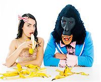 Woman Eating Banana Next to Sad Gorilla Man Stock Photo - Premium Royalty-Freenull, Code: 613-07067842