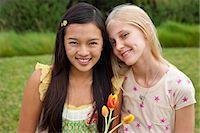 Teenage girls in garden, portrait, smiling Stock Photo - Premium Royalty-Freenull, Code: 613-07067892