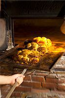 Freshly baked bread rolls on a baking tray in a wood-fired oven Stock Photo - Premium Royalty-Freenull, Code: 659-07068802