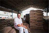 Man sitting on stack of wheat sacks in a warehouse, Anaj Mandi, Sohna, Gurgaon, Haryana, India Stock Photo - Premium Royalty-Freenull, Code: 630-07071194