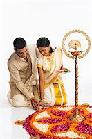 South Indian couple making a rangoli of flowers at Onam Stock Photo - Premium Royalty-Freenull, Code: 630-07071869