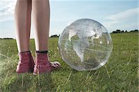 Girl standing in meadow with transparent globe Stock Photo - Premium Royalty-Freenull, Code: 628-07072092