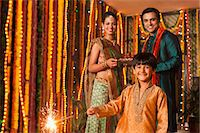 Boy burning fire crackers with his parents in the background on Diwali Stock Photo - Premium Royalty-Freenull, Code: 630-07072037