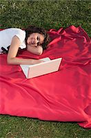 Girl using laptop on blanket Stock Photo - Premium Royalty-Freenull, Code: 628-07072115