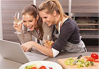 Two happy young women using laptop in kitchen Stock Photo - Premium Royalty-Freenull, Code: 628-07072517