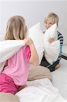 Brother and sister having a pillow fight in bed Stock Photo - Premium Royalty-Freenull, Code: 628-07072757