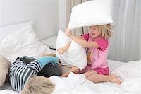 Brother and sister having a pillow fight in bed Stock Photo - Premium Royalty-Freenull, Code: 628-07072758