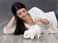 Young woman putting coin into piggy bank Stock Photo - Premium Royalty-Freenull, Code: 628-07072821