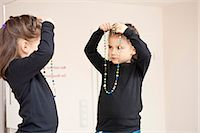 Girl with necklace looking in mirror Stock Photo - Premium Royalty-Freenull, Code: 628-07072964