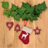 Christmas eve symbols of red stocking, tree, star and heart with ivy leaf sprigs over oak background. Stock Photo - Royalty-Freenull, Code: 400-07087002