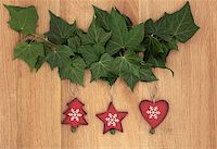 Old wooden christmas decorations hanging from ivy leaf sprigs over oak background. Stock Photo - Royalty-Freenull, Code: 400-07087007