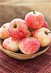 Fresh red apples in basket on the table and wooden background