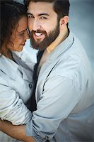 Image of happy man looking at camera while embracing his sweetheart Stock Photo - Royalty-Freenull, Code: 400-07101269