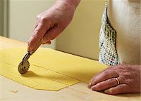 Close-up of elderly Italian woman making pasta by hand in kitchen, cutting pasta dough with rotary tool, Ontario, Canada Stock Photo - Premium Rights-Managednull, Code: 700-07108323