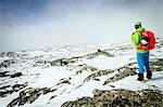 Speed hiker taking a look at mountain range, snowcapped, Norway, Europe