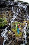 Hiker taking a look at waterfall, Norway, Europe
