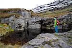 Hiker looking at fjord, Norway, Europe