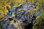 Hiker stands on rock, looking at canyon, Norway, Europe