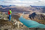 Hiker taking a look at fjord in mountain scenery, Norway, Europe