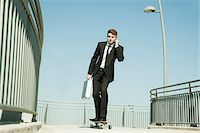 Businessman using Cell Phone while Skateboarding, Mannheim, Baden-Wurttemberg, Germany Stock Photo - Premium Royalty-Freenull, Code: 600-07110820