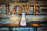Image of a wedding cake with the word love as sinage on a rustic background Stock Photo - Royalty-Freenull, Code: 400-07111194