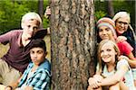 Portrait of group of children posing next to tree in park, Germany