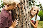 Boy and Girl playing outdoors standing next to tree in park, Germany