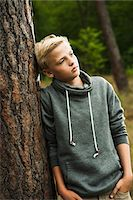 Portrait of boy standing in front of tree in park, looking into the distance, Germany Stock Photo - Premium Royalty-Freenull, Code: 600-07117123