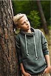 Portrait of boy standing in front of tree in park, looking into the distance, Germany Stock Photo - Premium Royalty-Free, Artist: Uwe Umstätter, Code: 600-07117123