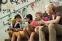 Group of children sitting on stairs outdoors, using tablet computers and smartphones, Germany Stock Photo - Premium Royalty-Freenull, Code: 600-07117174