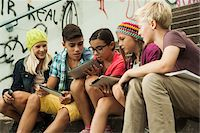 Group of children sitting on stairs outdoors, using tablet computers and smartphones, Germany Stock Photo - Premium Royalty-Freenull, Code: 600-07117175