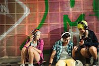 Children sitting next to wall outdoors, wearing headphones and listening to music, Germany Stock Photo - Premium Royalty-Freenull, Code: 600-07117177