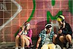 Children sitting next to wall outdoors, wearing headphones and listening to music, Germany Stock Photo - Premium Royalty-Free, Artist: Uwe Umstätter, Code: 600-07117177
