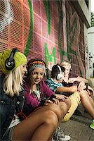 Group of children sitting next to wall outdoors, wearing headphones and listening to music, Germany Stock Photo - Premium Royalty-Freenull, Code: 600-07117181
