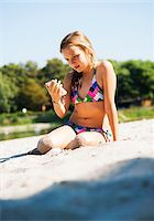 Girl using Cell Phone at Beach, Lampertheim, Hesse, Germany Stock Photo - Premium Royalty-Freenull, Code: 600-07117301