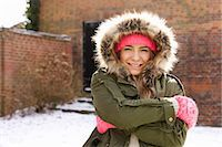 Smiling Teenage Girl Wearing Parka Hugging Herself Outdoors Stock Photo - Premium Rights-Managednull, Code: 822-07117402