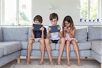 Brothers and sister on sofa with digital tablets and mobile Stock Photo - Premium Royalty-Freenull, Code: 649-07118650