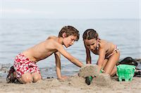 preteen swimsuit - Brother and sister on beach building sandcastle Stock Photo - Premium Royalty-Freenull, Code: 649-07118653