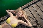 Young woman lying on pier
