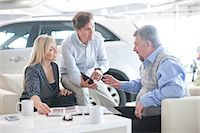 Car salesman talking to couple in car showroom Stock Photo - Premium Royalty-Freenull, Code: 649-07119148