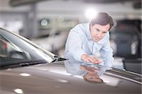 Mid adult man looking at car bonnet in showroom Stock Photo - Premium Royalty-Freenull, Code: 649-07119156