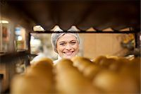 Portrait of young baker and tray of bread rolls Stock Photo - Premium Royalty-Freenull, Code: 649-07119162