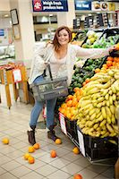 Young woman having shopping mishap with oranges Stock Photo - Premium Royalty-Freenull, Code: 649-07119173