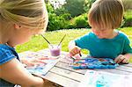 Brother and sister finger painting in garden Stock Photo - Premium Royalty-Freenull, Code: 649-07119205
