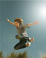 Teenage boy jumping against clear blue sky Stock Photo - Premium Royalty-Freenull, Code: 649-07119689