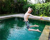 Boy jumping into swimming pool Stock Photo - Premium Royalty-Freenull, Code: 649-07119725