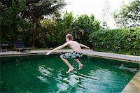 Boy jumping into swimming pool Stock Photo - Premium Royalty-Freenull, Code: 649-07119727